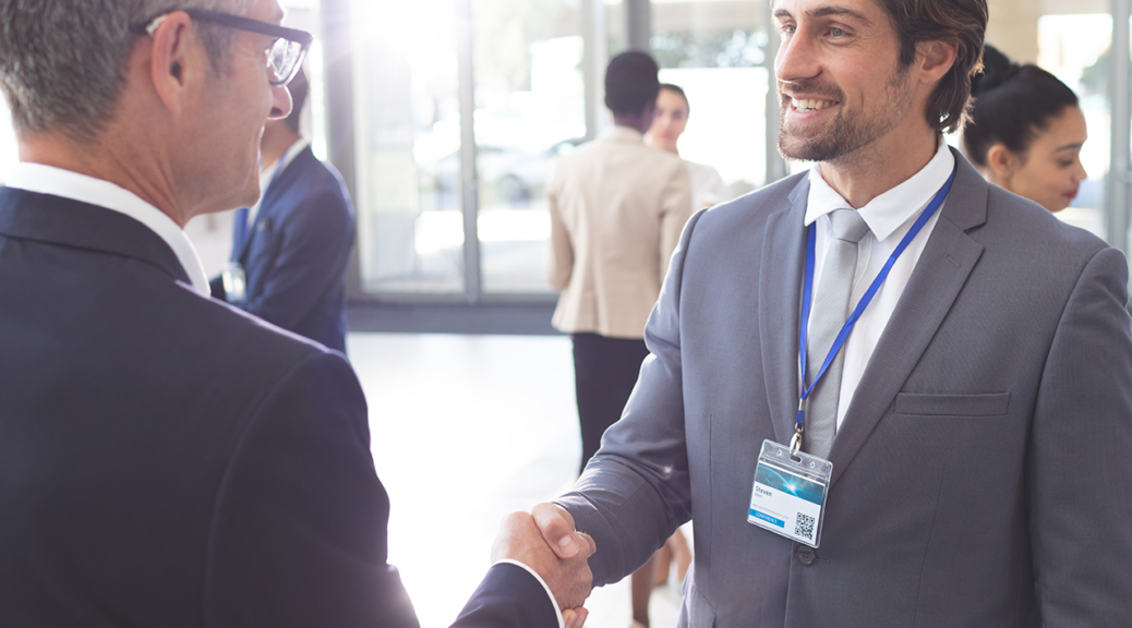 Two people shaking hands networking together.